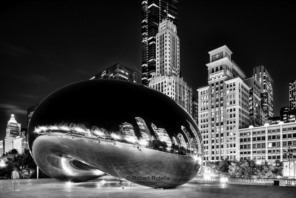 The Bean reflects the skyline in this Chicago Nightscape. Millennium Park, Chicago, Illinois. People are ghosted in the long exposure.